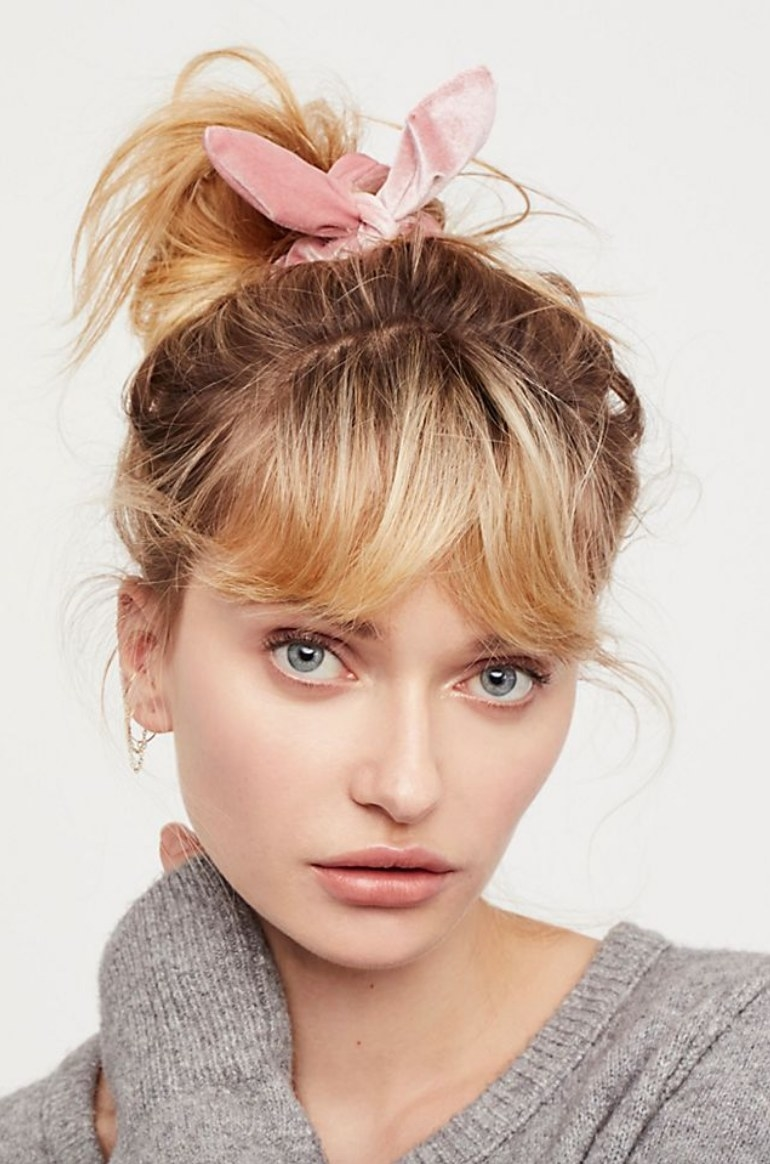 Model wearing messy bun with pink knotted velvet scrunchie