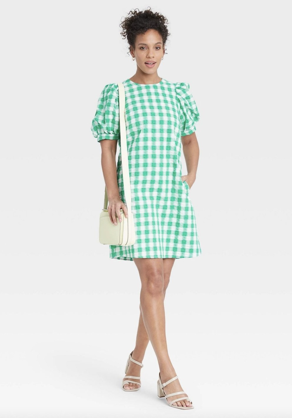 A woman wearing a green and white gingham print dress with tan sandals