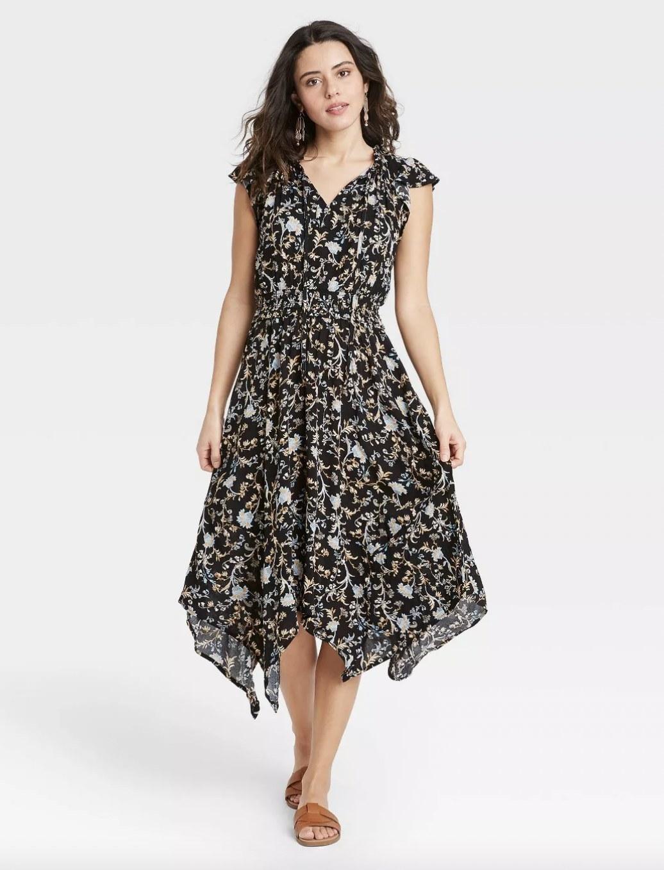 A woman wearing a black floral dress
