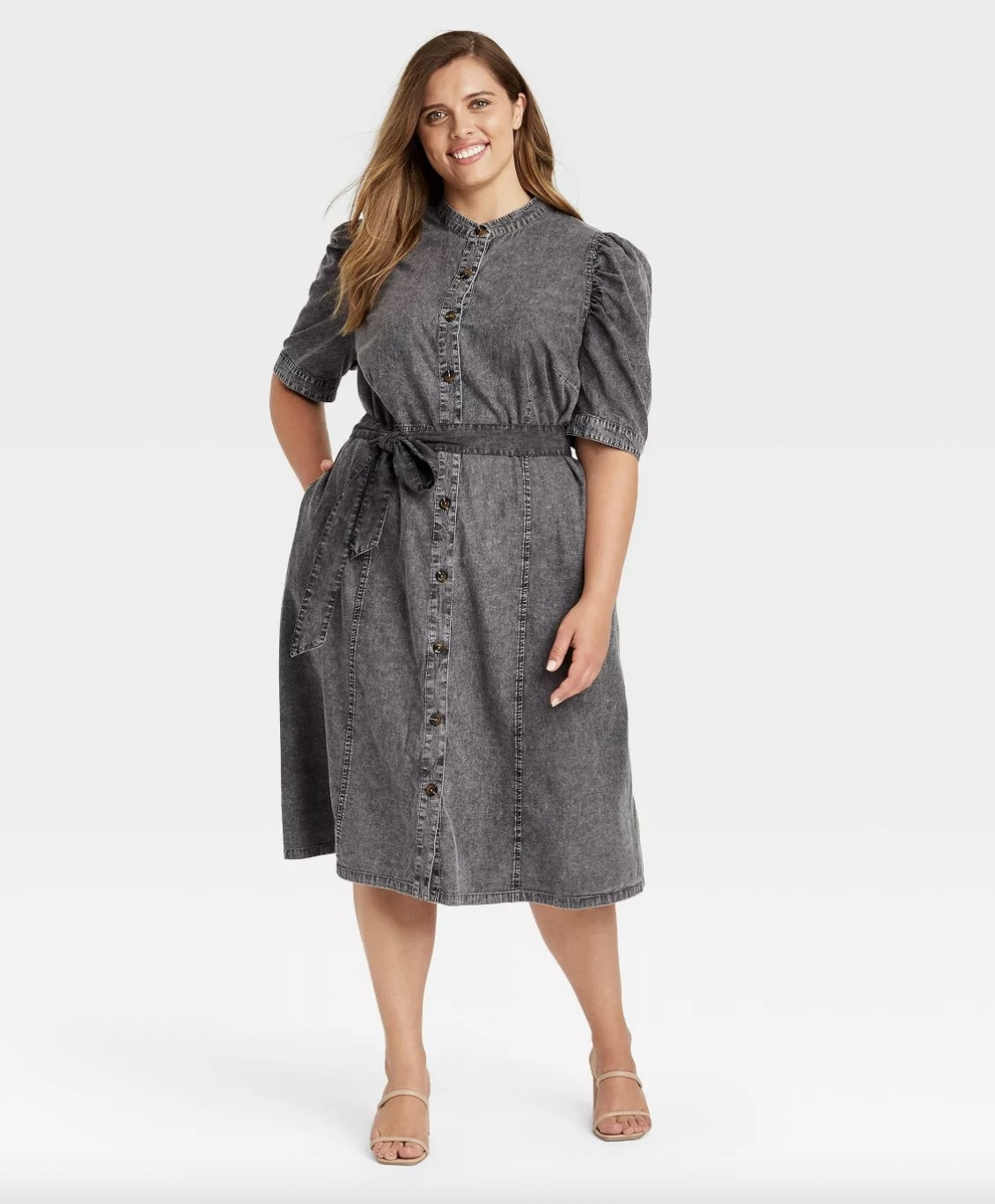 A woman wearing a grey denim dress with puff sleeves and sandals