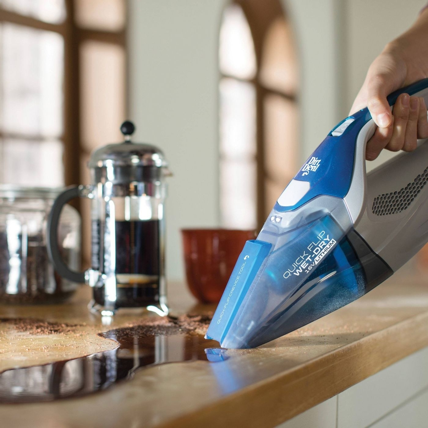Blue and silver wet-dry vac cleaning up spilled coffee on the counter