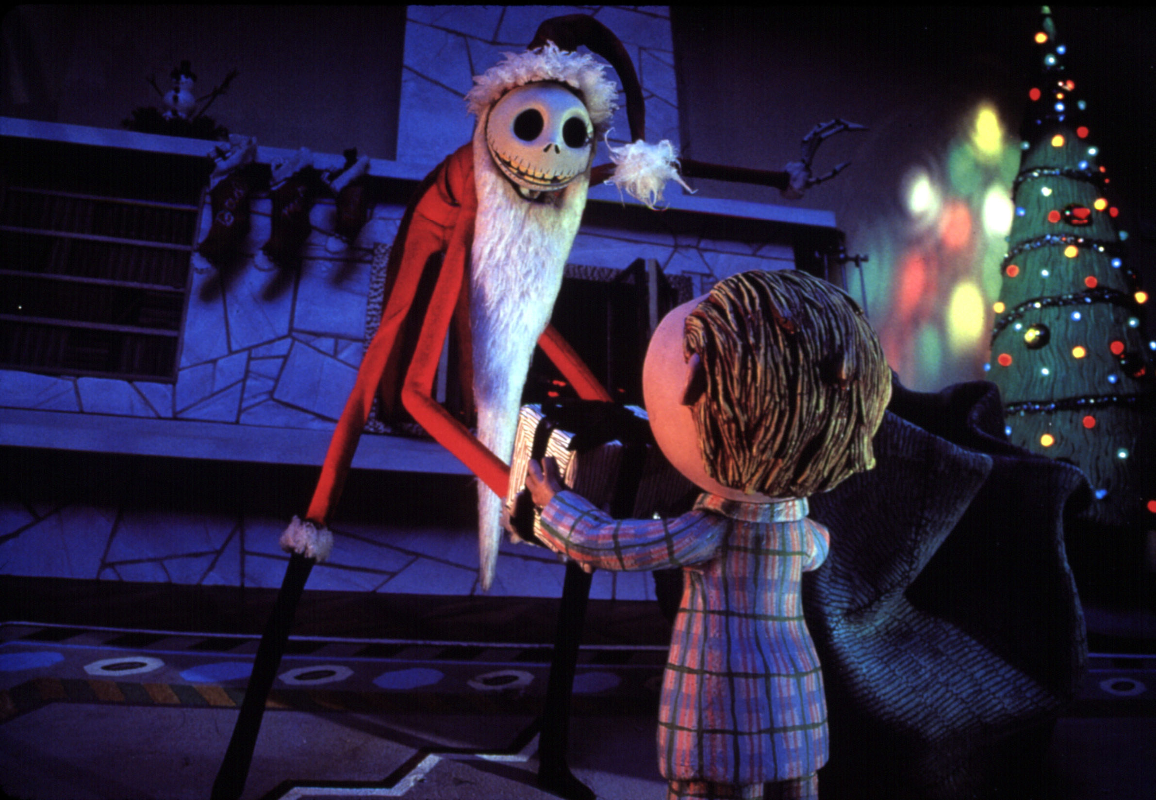 Jack Skellington dressed as Santa Claus handing a gift to a child