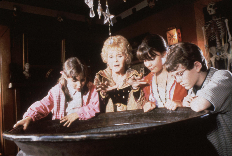 Emily Roeske, Debbie Reynolds, Kimberly J. Brown, Joey Zimmerman looking over a cauldron in Halloweentown
