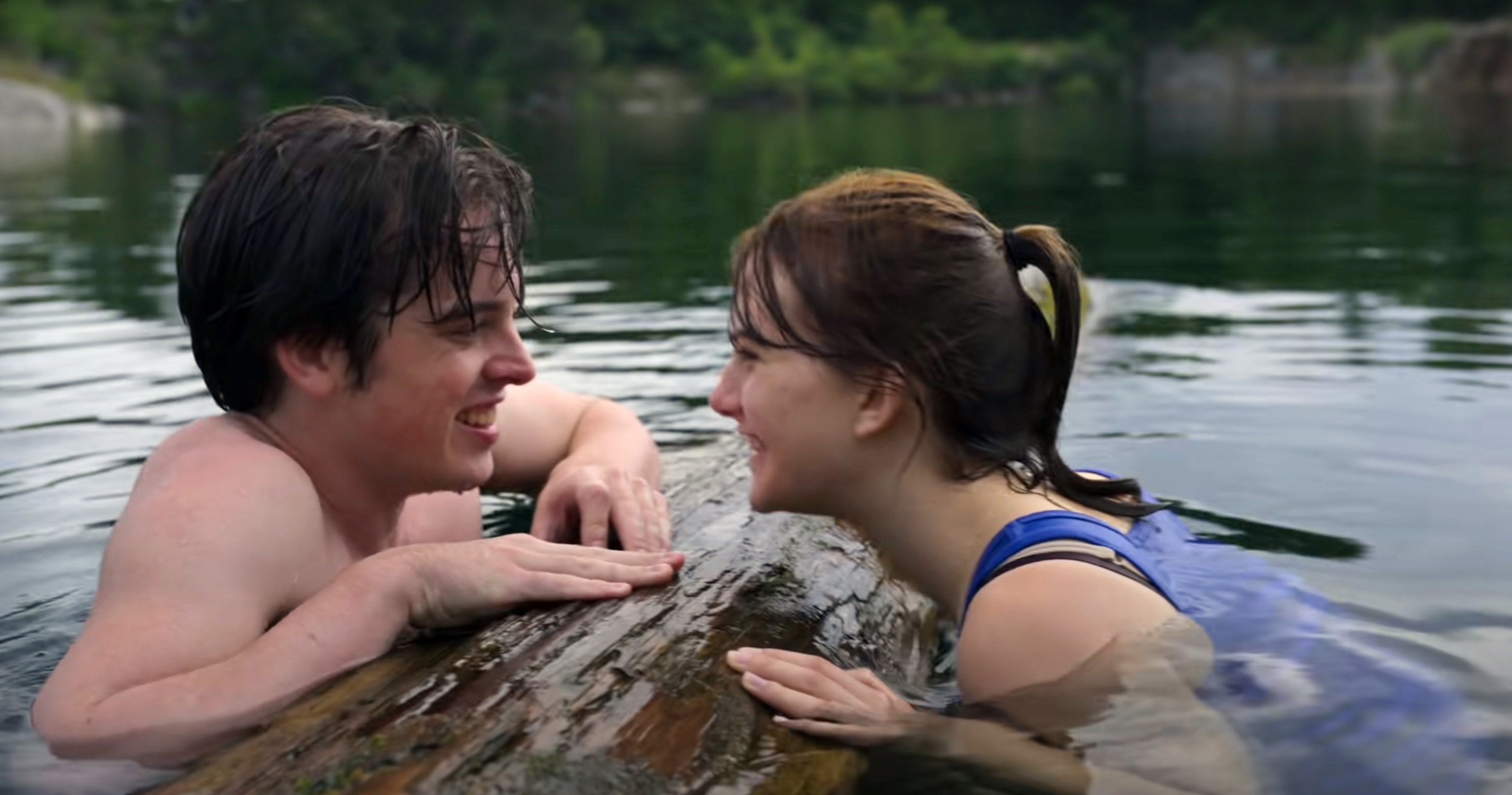 Ferdia Walsh-Peelo and Emilia Jones lean on a log in the water together