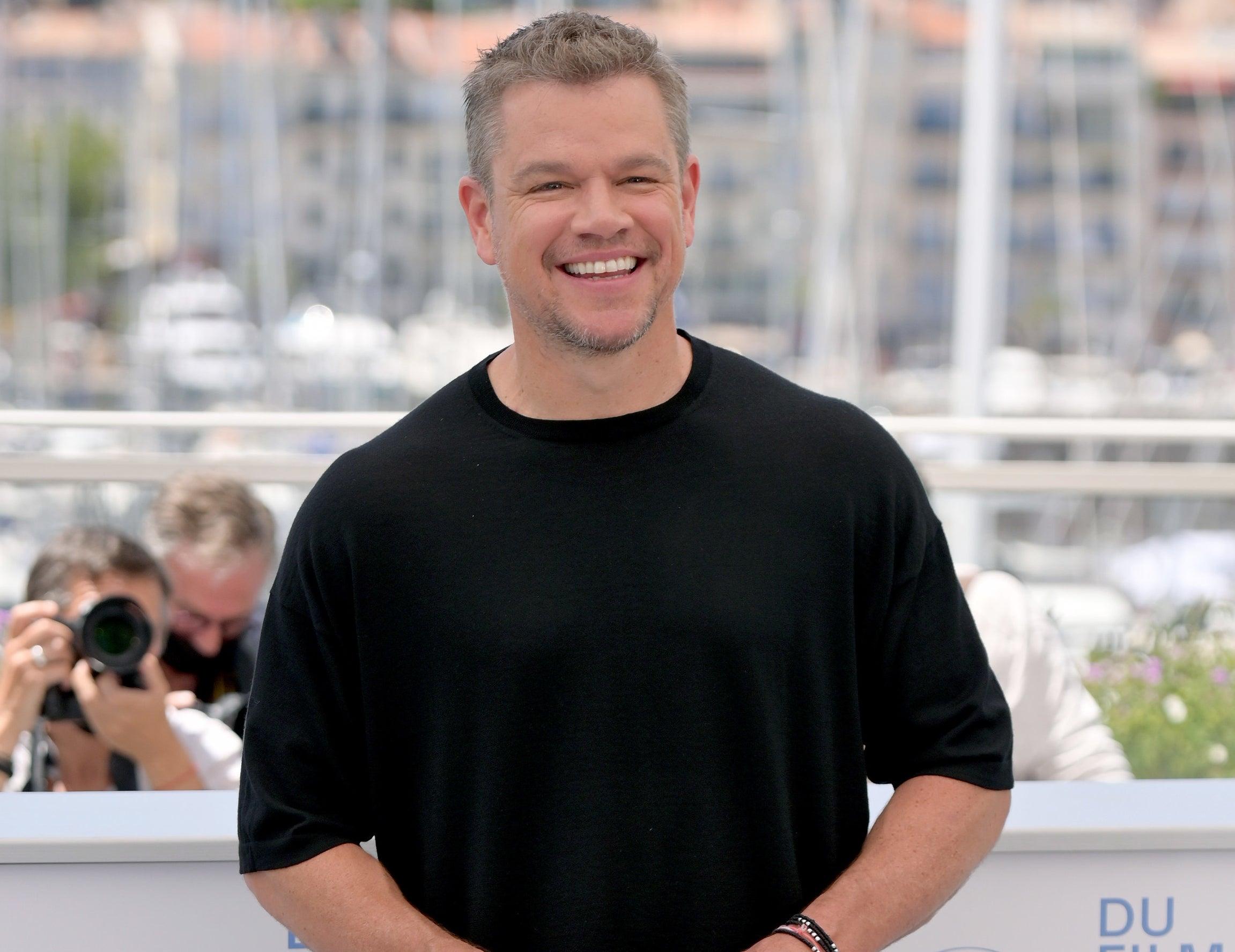 Matt laughs while wearing a black t-shirt outside