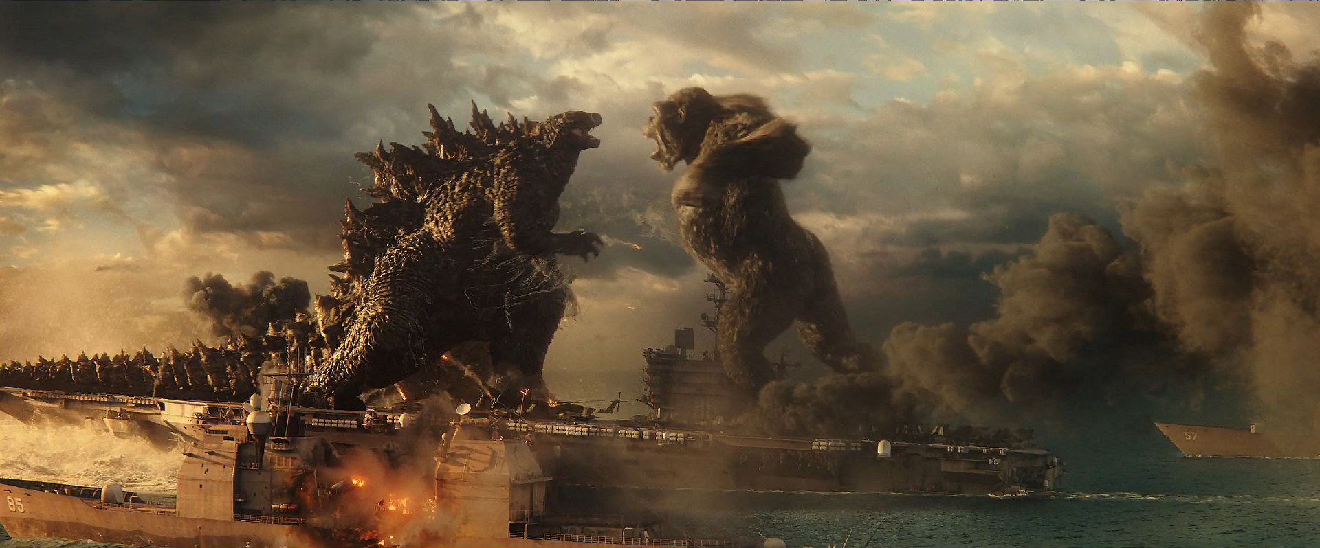 Godzilla and King Kong prepare to clash above a smoking battle ship