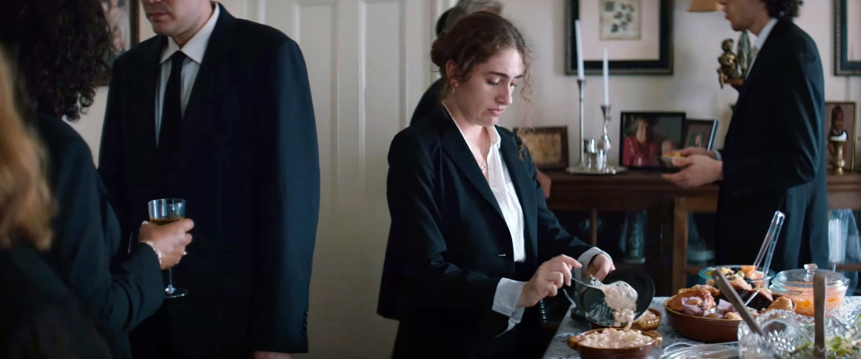 Rachel Sennott scoops food onto a plate