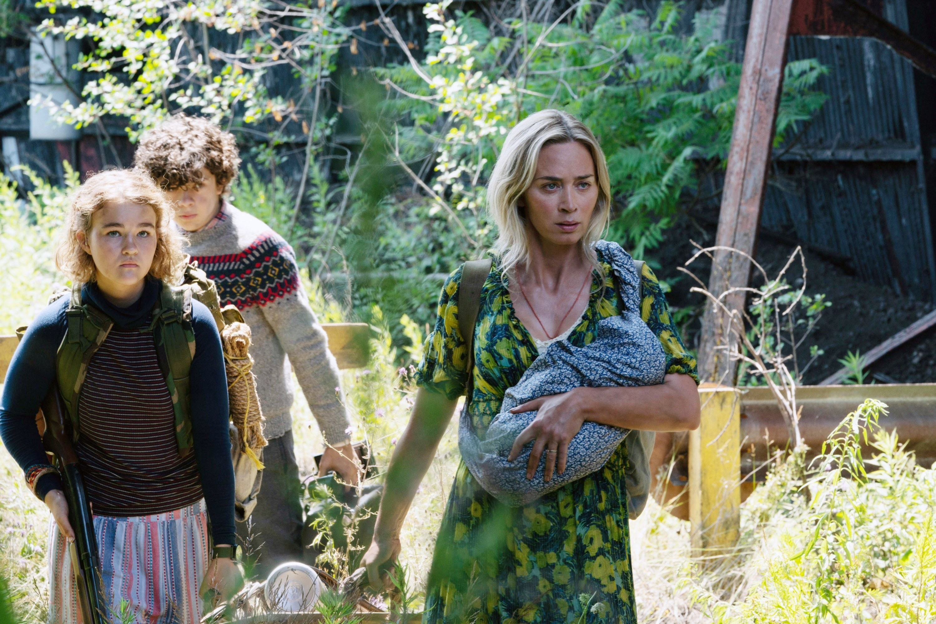 Emily Blunt carries a baby and leads Millicent Simmonds and Noah Jupe through some weeds
