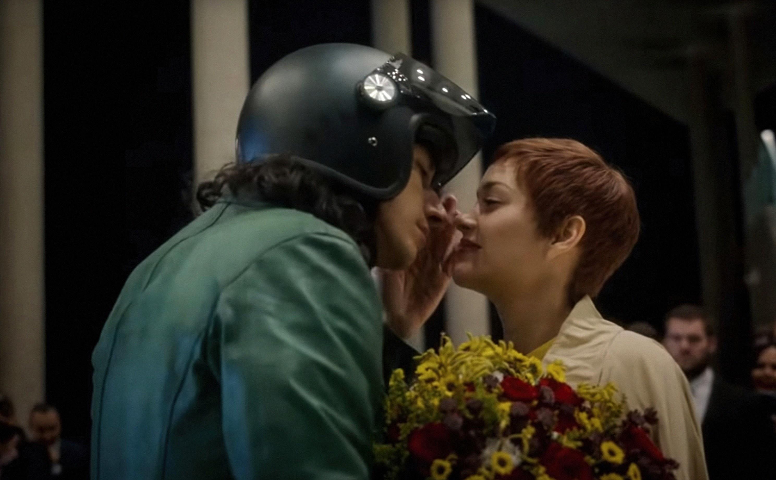 Marion Cotillard holding flower prepares to kiss Adam Driver in a motorcycle helmet