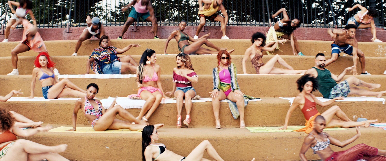 Stephanie Beatriz, Daphne Rubin-Vega, and Dascha Polanco sit amid posing sunbathers near a pool