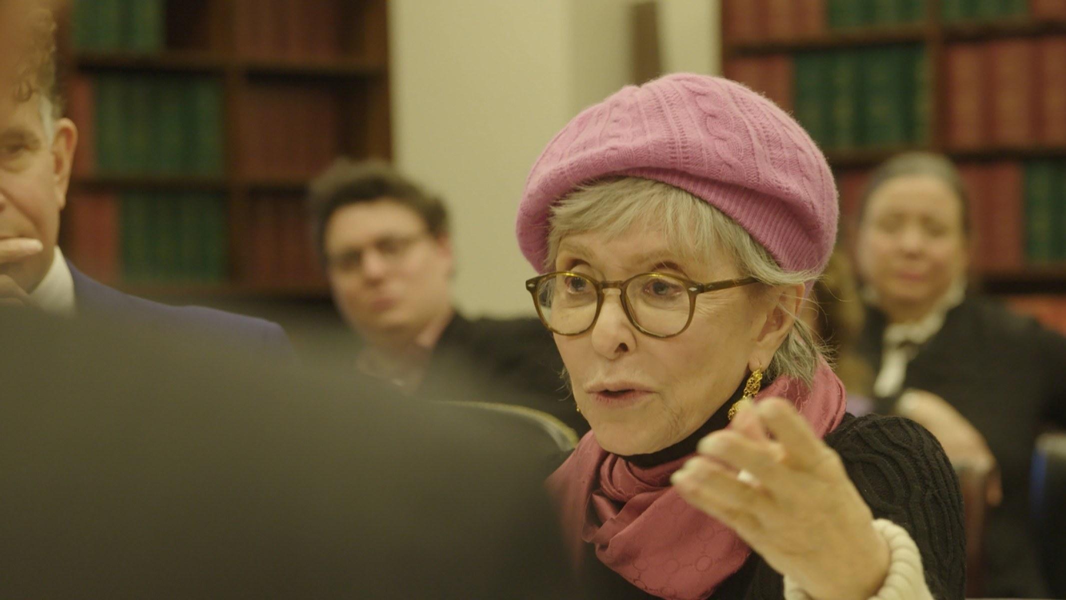 Rita Moreno speaks while wearing a pink hat