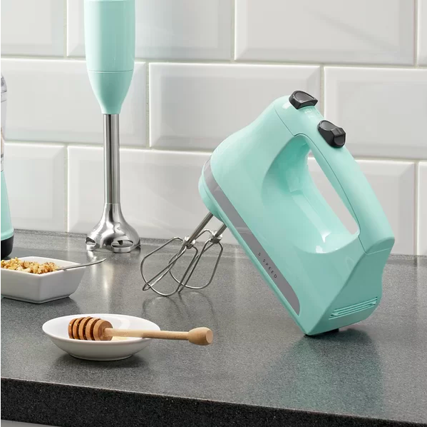 the KitchenAid hand mixer in turquoise on a counter