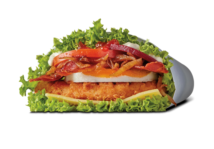 Fried chicken topped with an egg, bacon, tomatoes, ketchup, mayo, cheese, caramel onions, and wrapped in lettuce