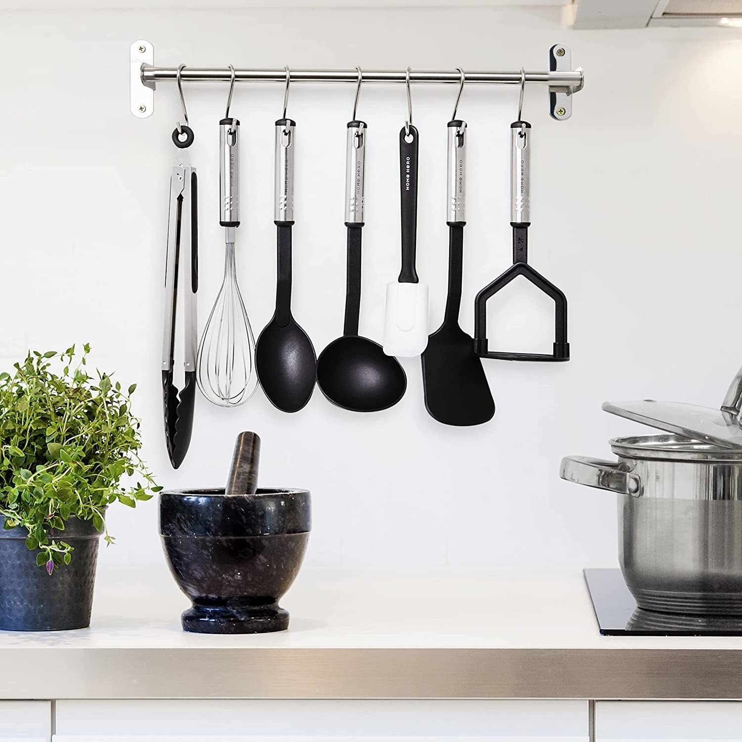 kitchen utensils hanging from a rack above a countertop