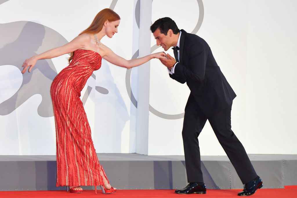 """Oscar Isaac leans down to kiss Jessica Chastain on the hand on the red carpet of the movie """"Scenes From a Marriage (Ep. 1 and 2)"""""""