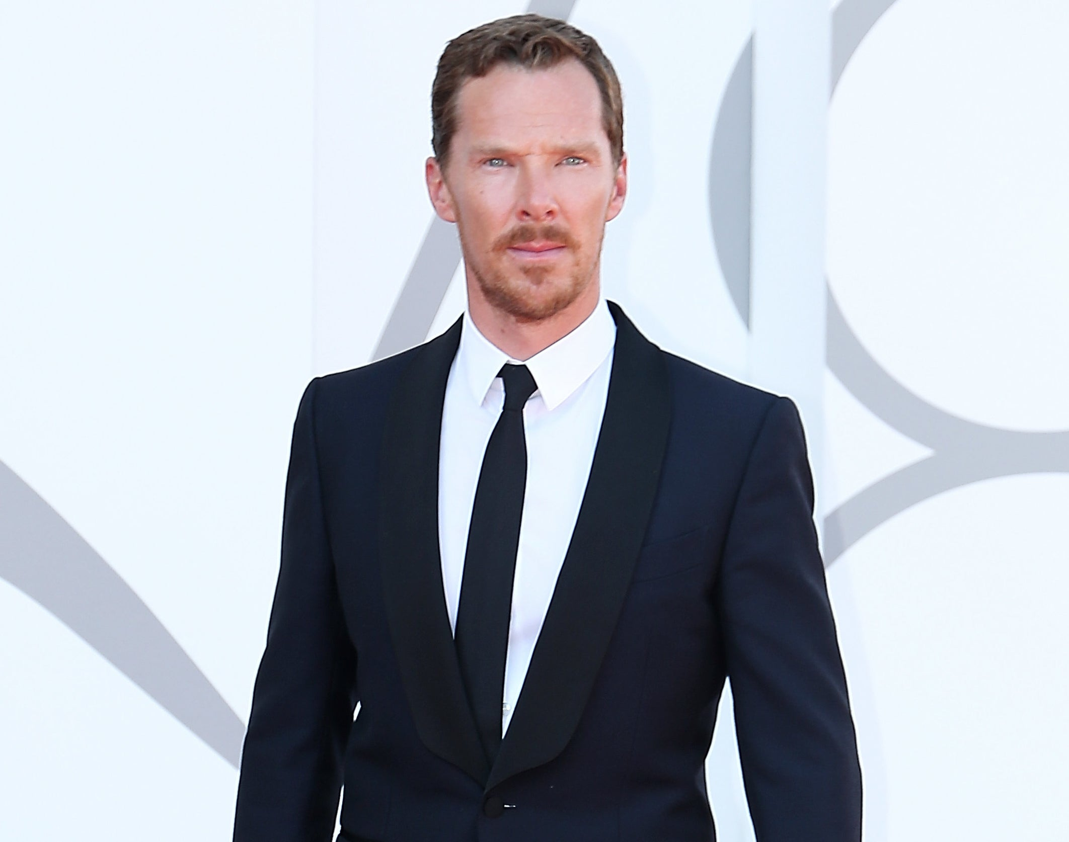 Benedict wears a black suit and skinny black tie