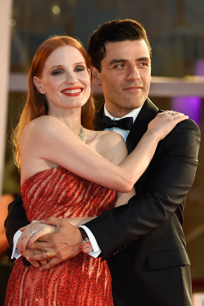Jessica Chastain (L) and Oscar Isaac holding each other on the red carpet