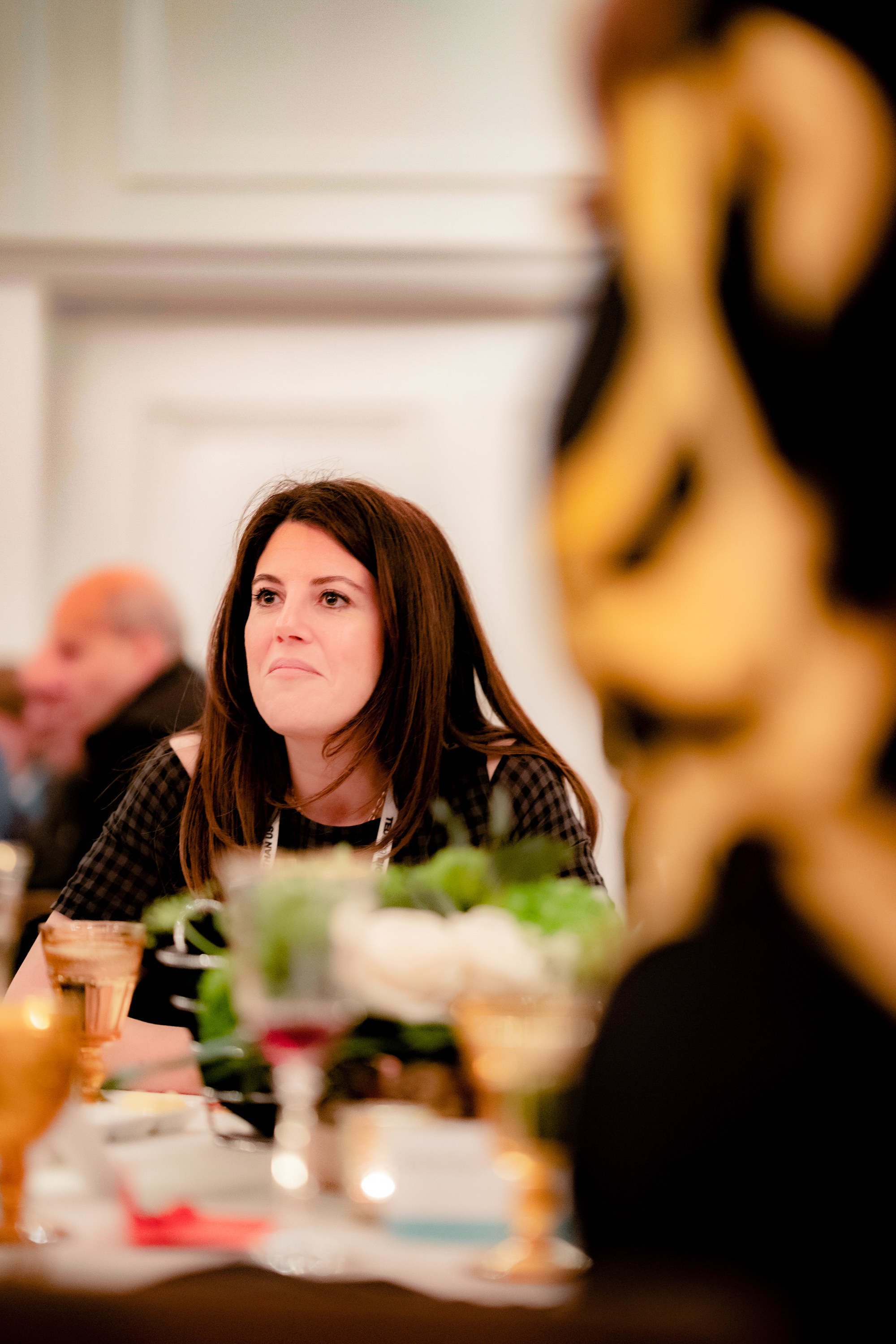 Lewinsky sits at a table during a dinner