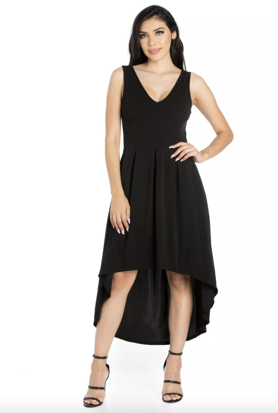 A woman wearing a black dress and sandals