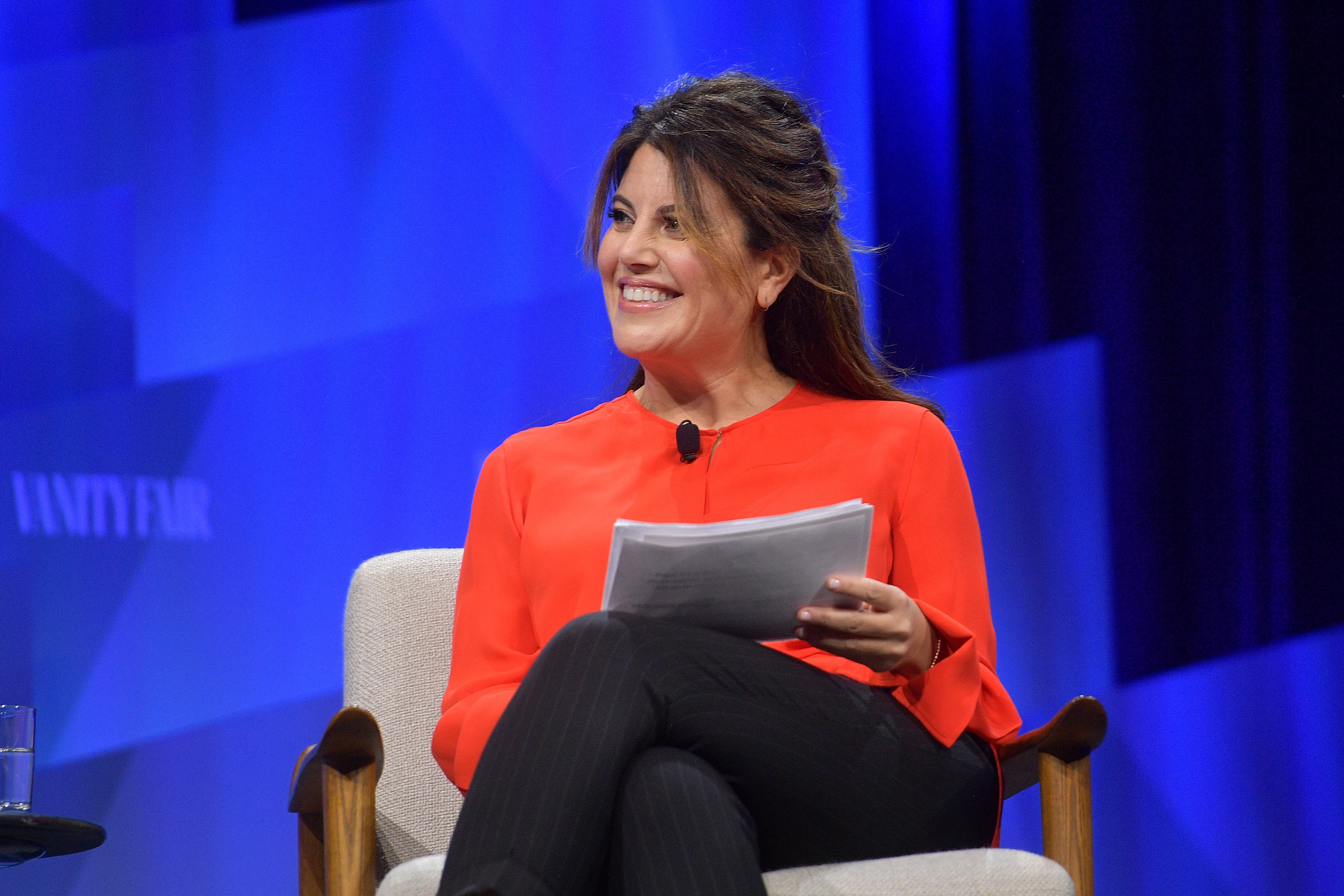 Lewinsky smiles while sitting in a chair and holding a sheath of papers