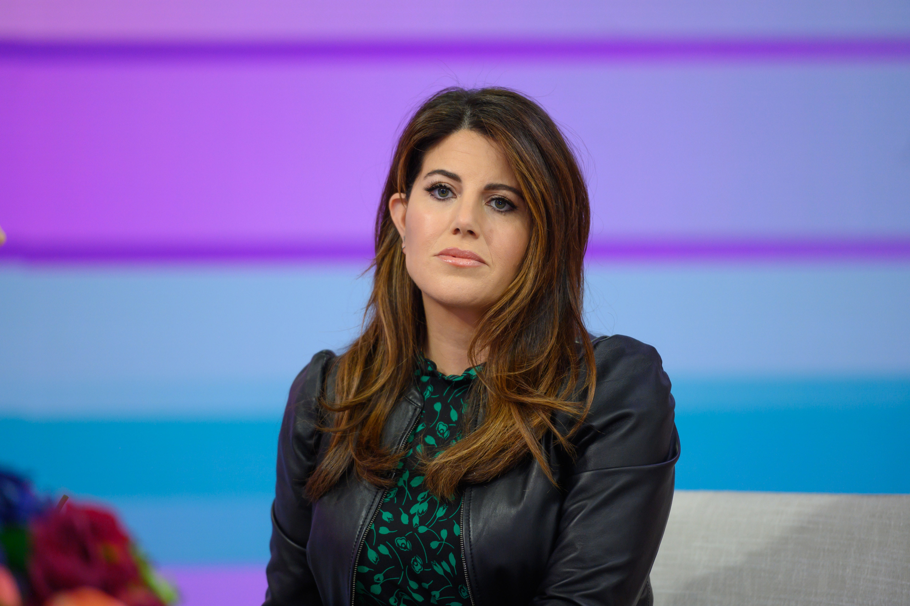 Lewinsky sits in a chair and looks in the distance