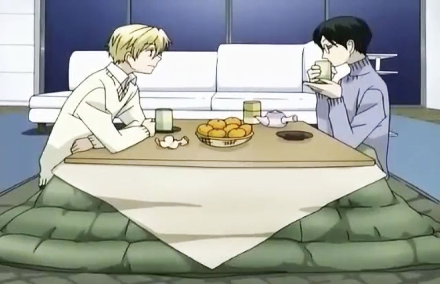 Two anime characters sitting at a low dining table drinking green tea; the table is covered by a kotatsu