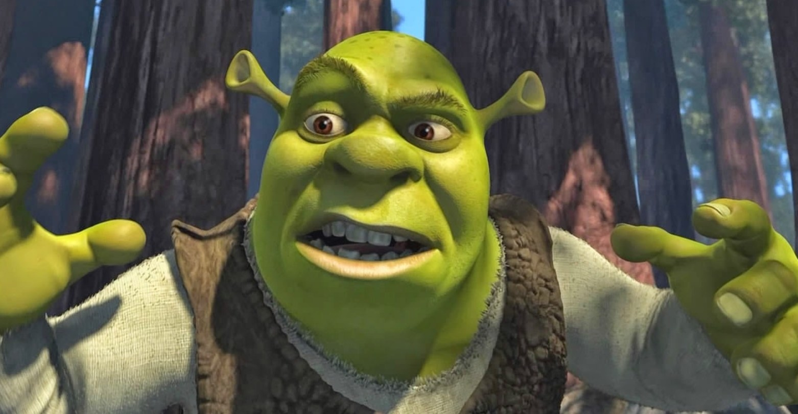 Shrek stands in the woods and gestures while talking