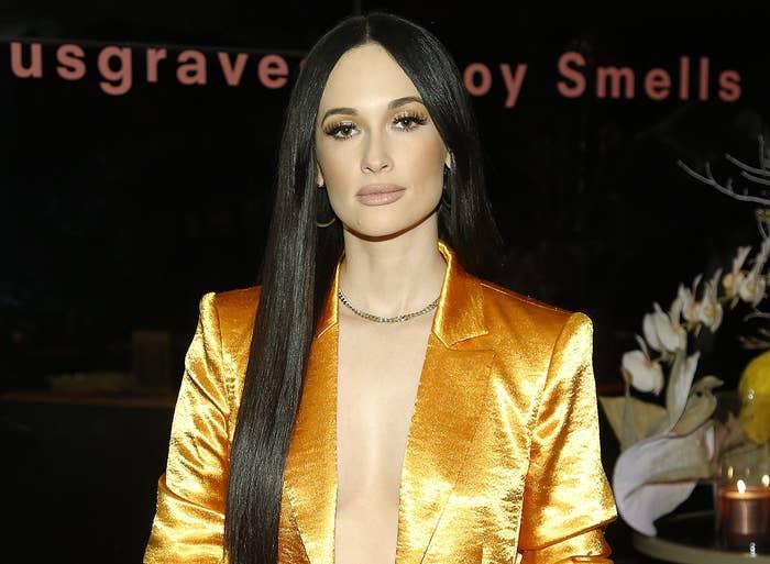 Kacey wear a shiny satin orange blazer with no shirt underneath