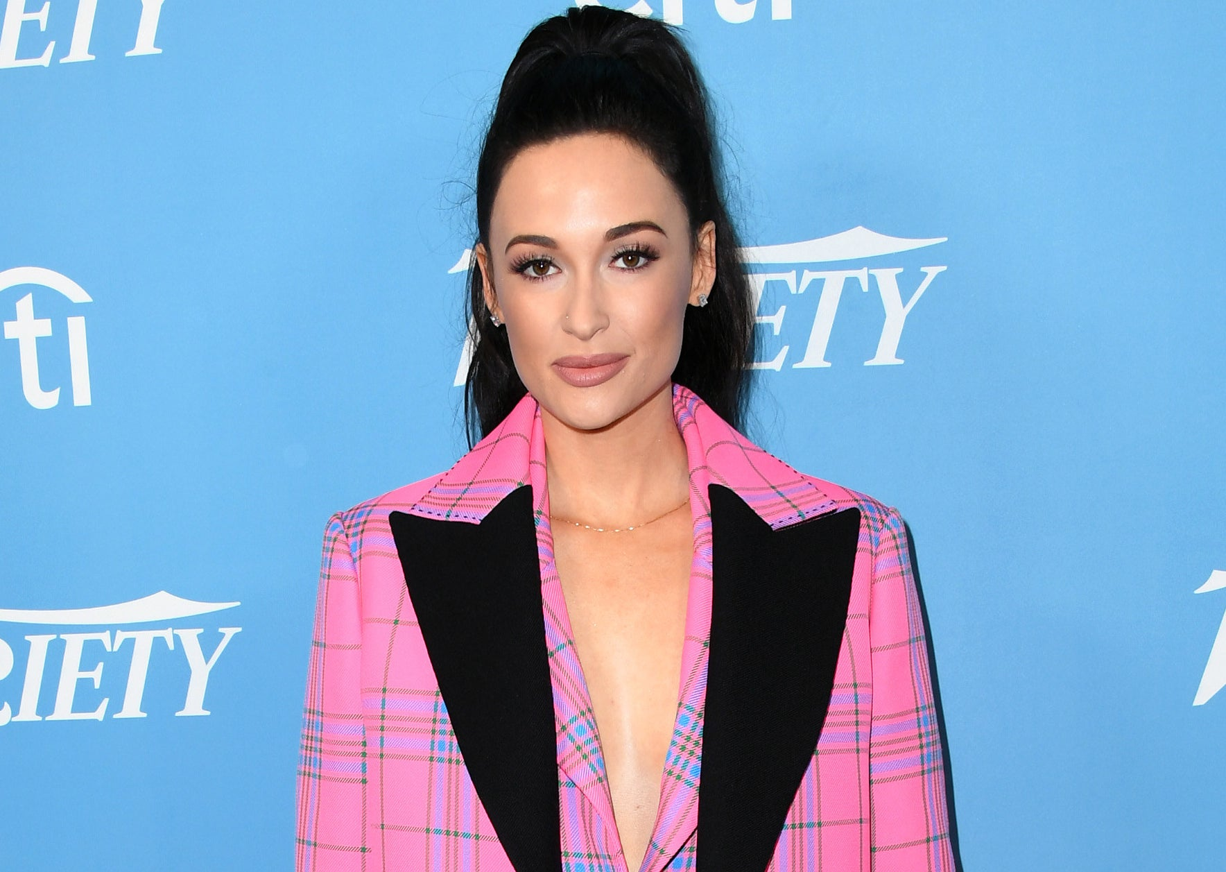 Kacey wears her hair up and pink plaid blazer