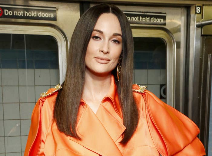Kacey stands on a subway while wearing a billowing orange dress