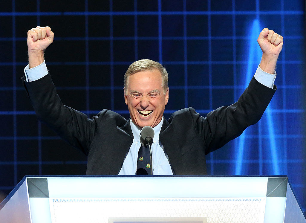 Howard Dean lifting his arms in excitement behind a podium