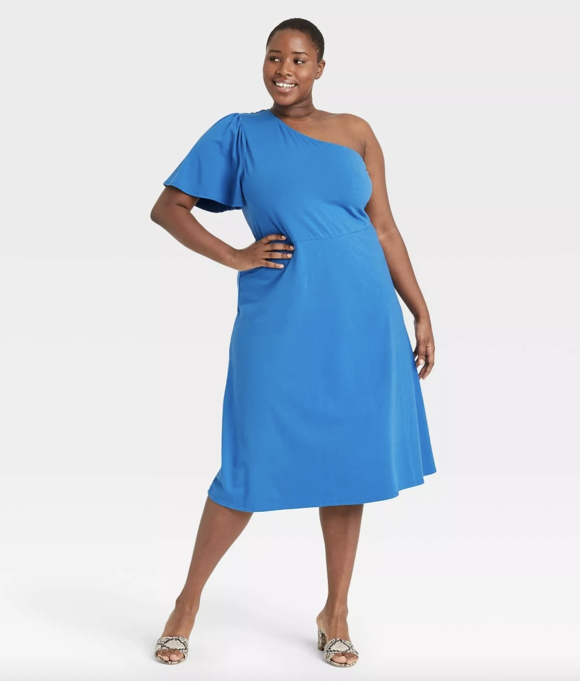 A woman wearing a blue one-shoulder dress