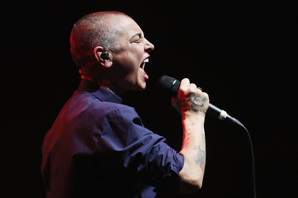 Sinead O'Connor performing on stage, singing into the microphone
