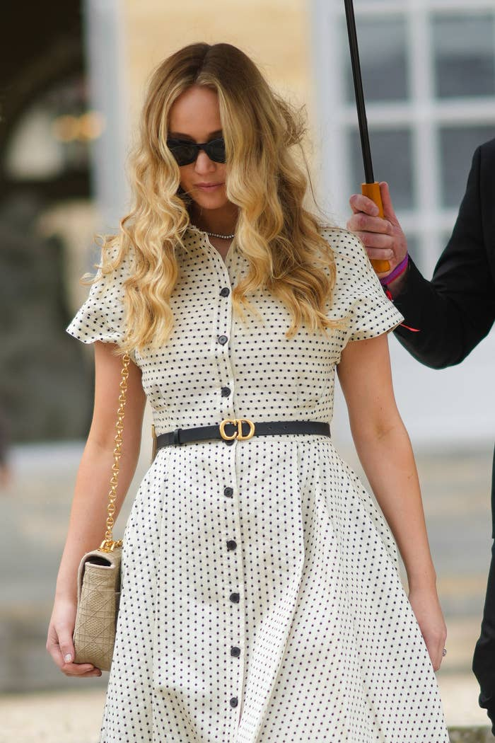 Jennifer Lawrence walks down stairs while wearing a polka-dot dress with a clutch at her side