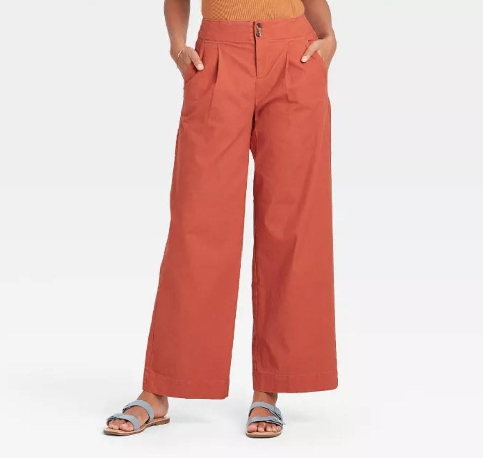 a model wearing the pants in orange
