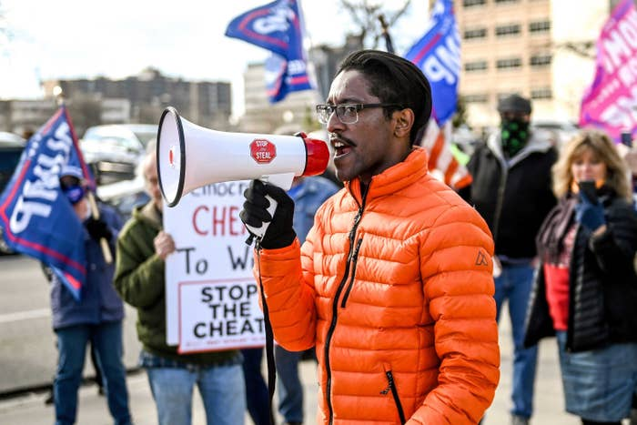 Ali Alexander speaking into a megaphone in front of other demonstrators