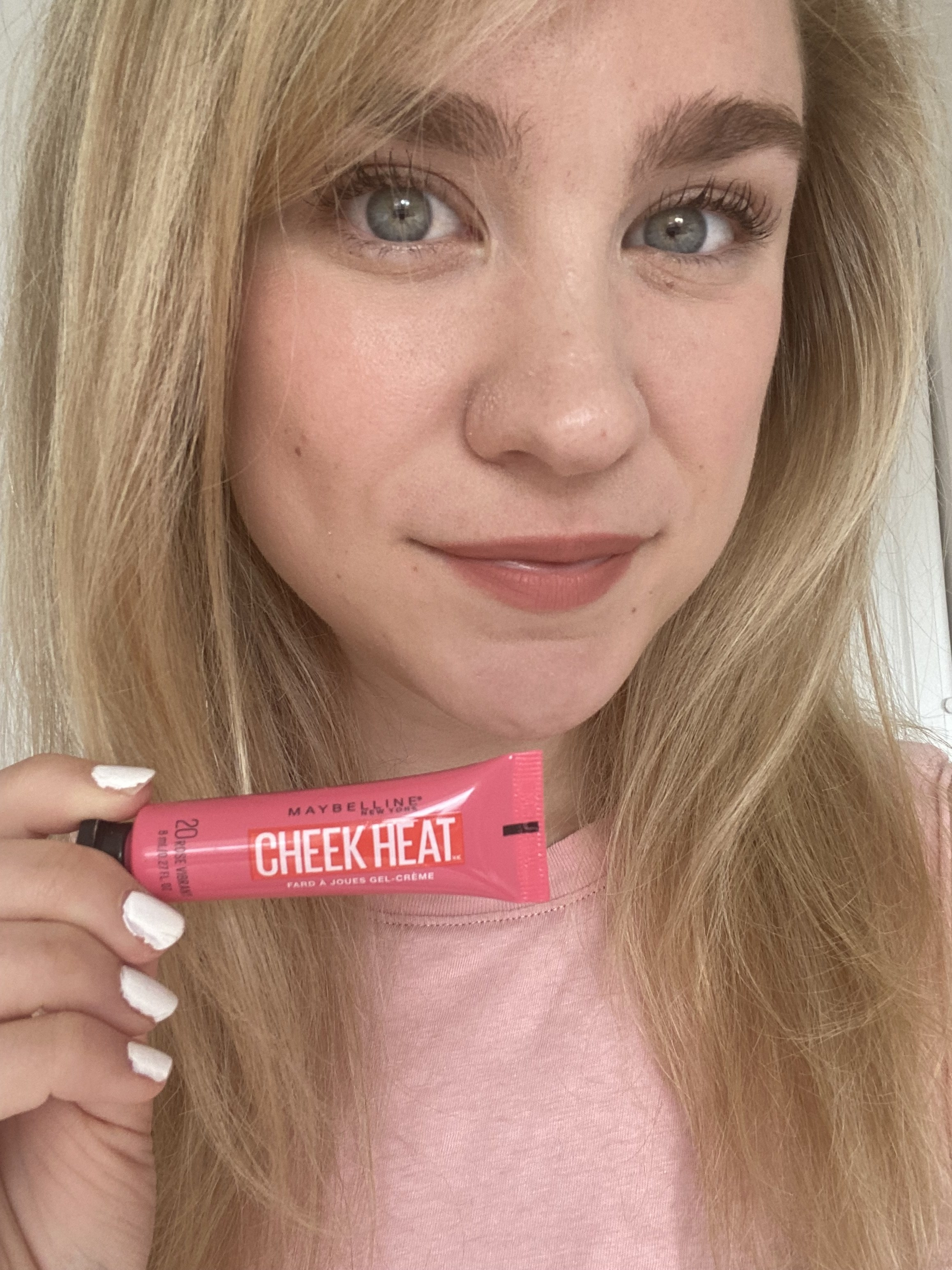 BuzzFeed editor holding pink tube of Cheek Heat with it applied to cheeks