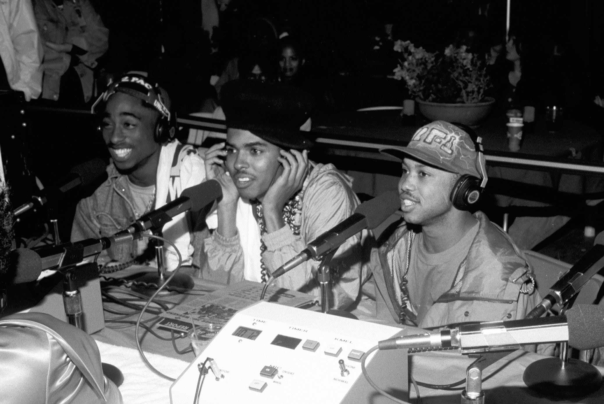 Three men smile and lean forward to talk into microphones