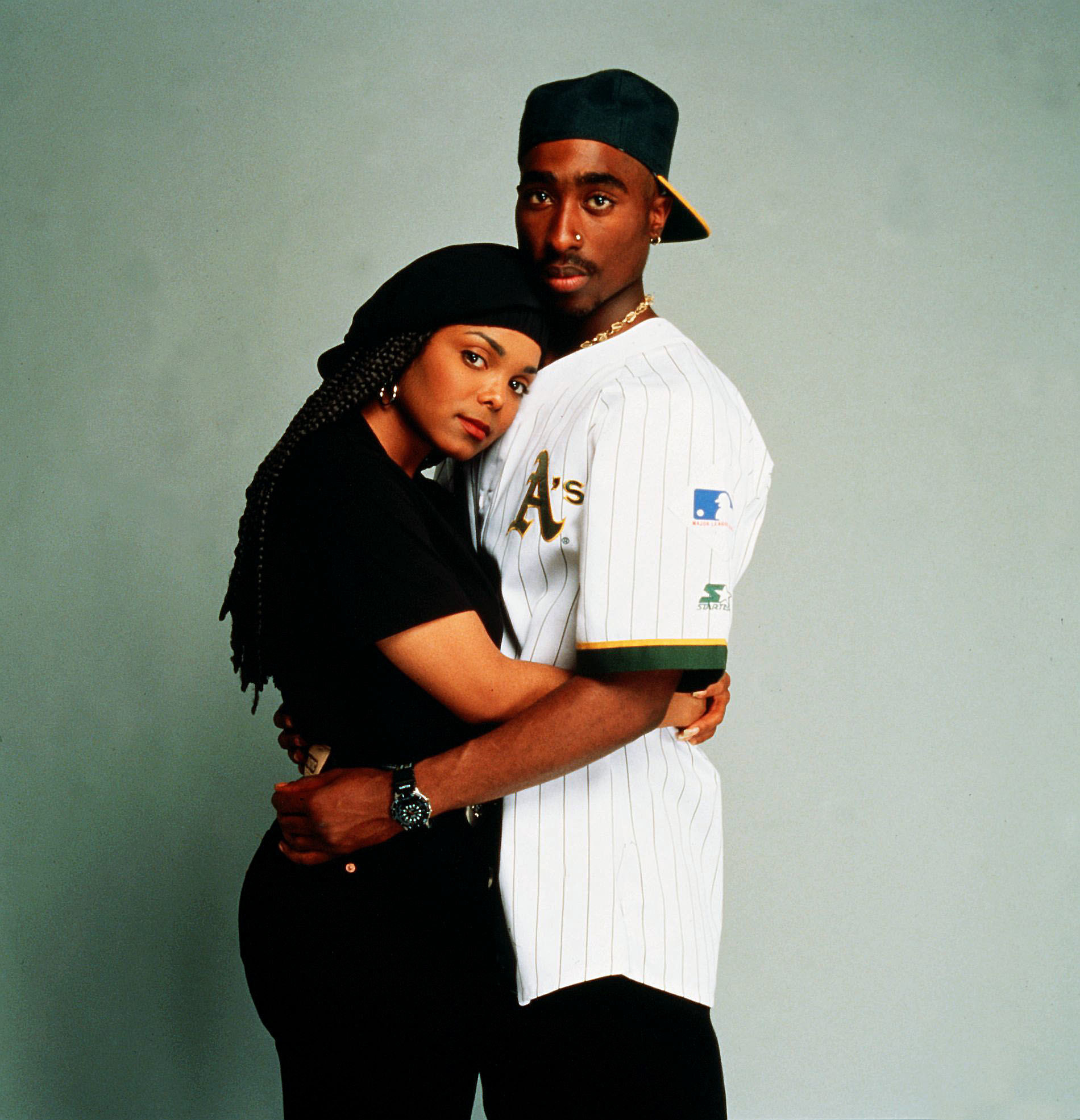 Tupac, wearing an Oakland A's jersey, holds Janet Jackson in a photo studio