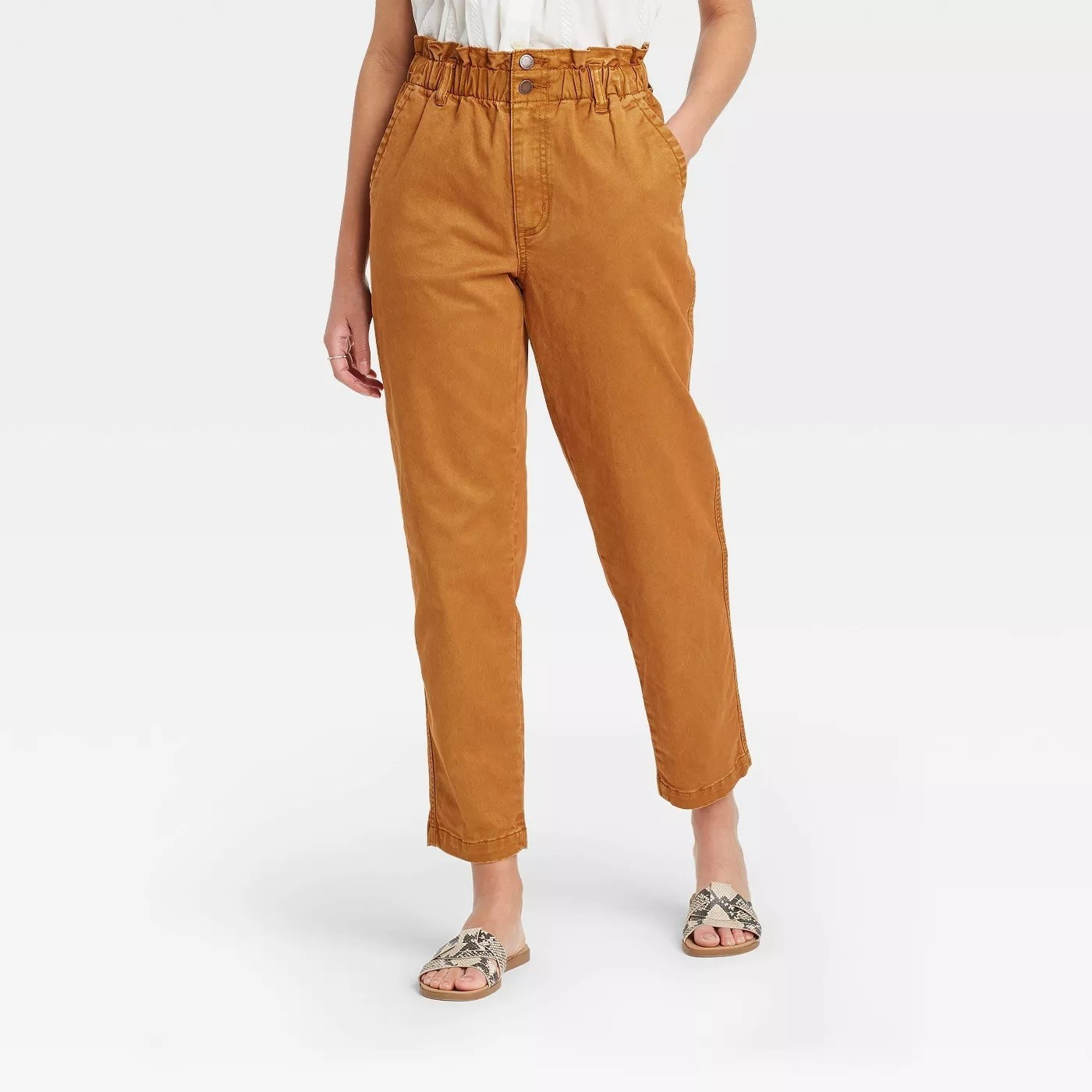Model wearing mustard yellow pants with two pockets, stops at ankle