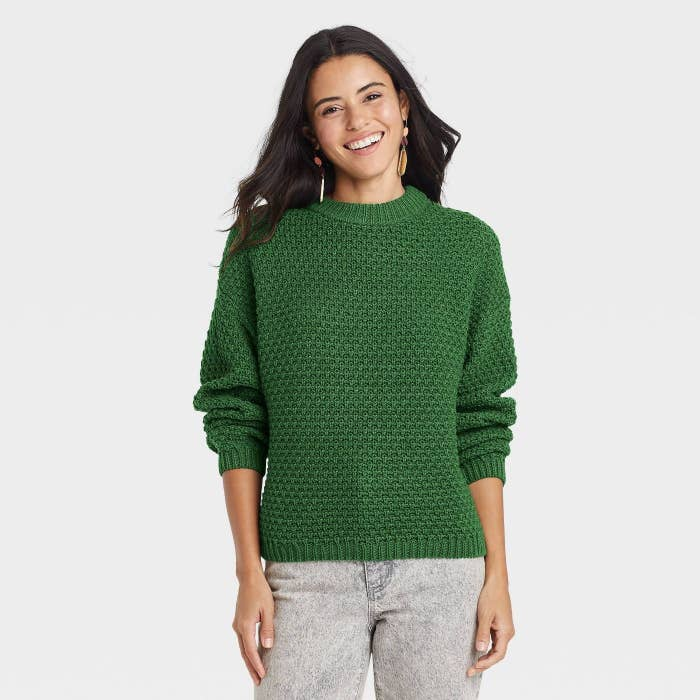 model wearing green sweater with acid wash grey jeans