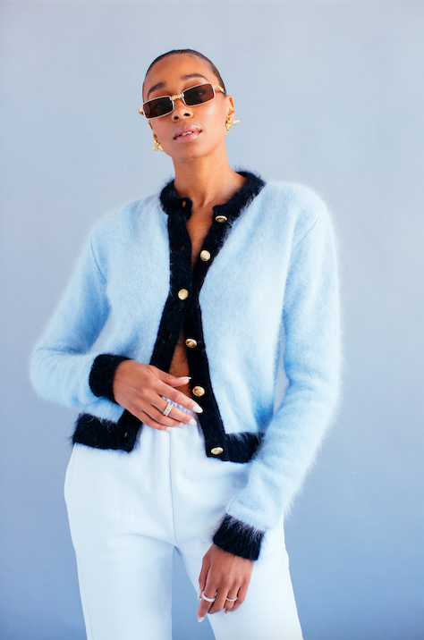 model in square-shaped brown sunglasses and a fluffy blue cardigan and white pants
