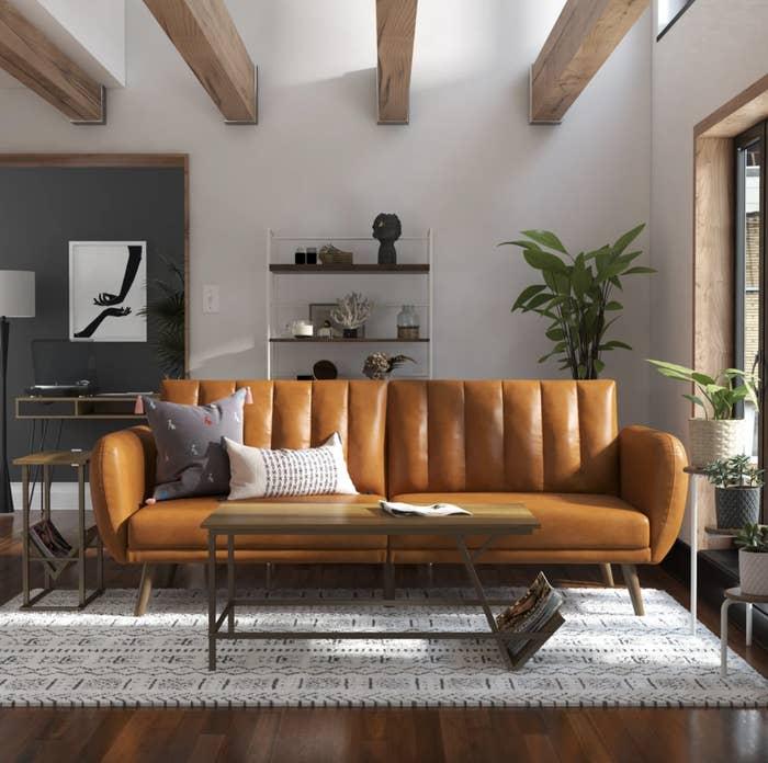 The Novogratz futon is shown in a creamy brown faux leather