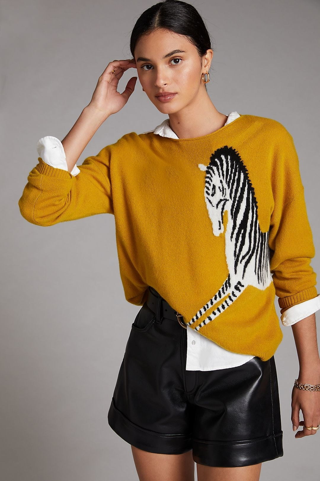 model wearing the yellow sweater with a white shirt underneath and black leather shorts