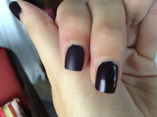 reviewer's nails, one with regular shiny black polish and one matte black