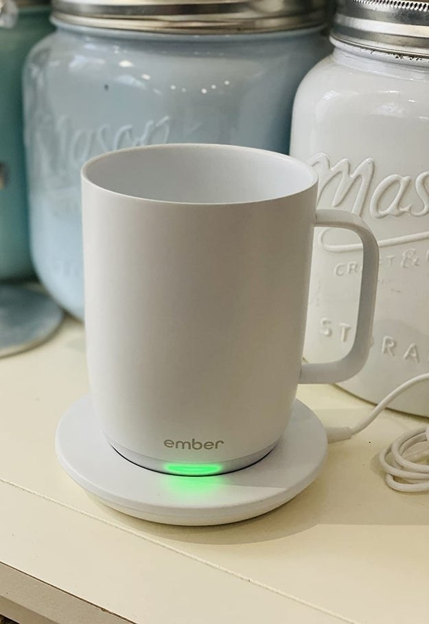 reviewer image of the white ember mug charging on its coaster