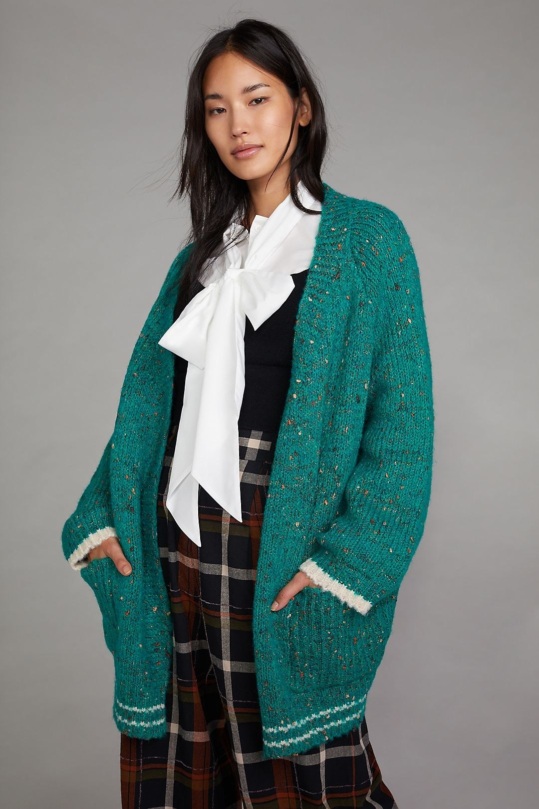 modwel wearing the green sweater over a black and white top and plaid pants