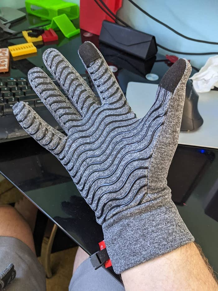 a reviewer's hand with the gray touchscreen glove on