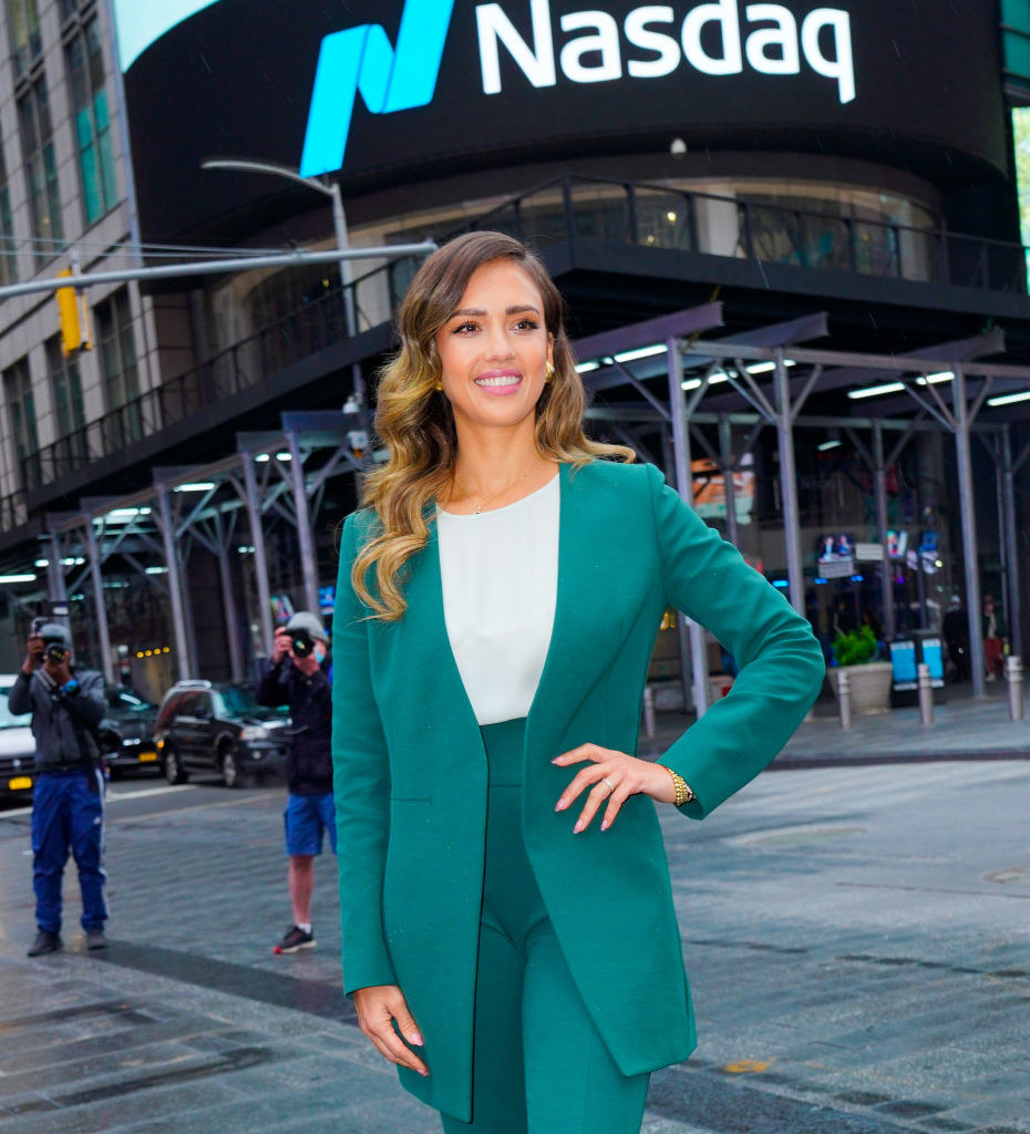 Jessica standing in front of a digital NASDAQ sign