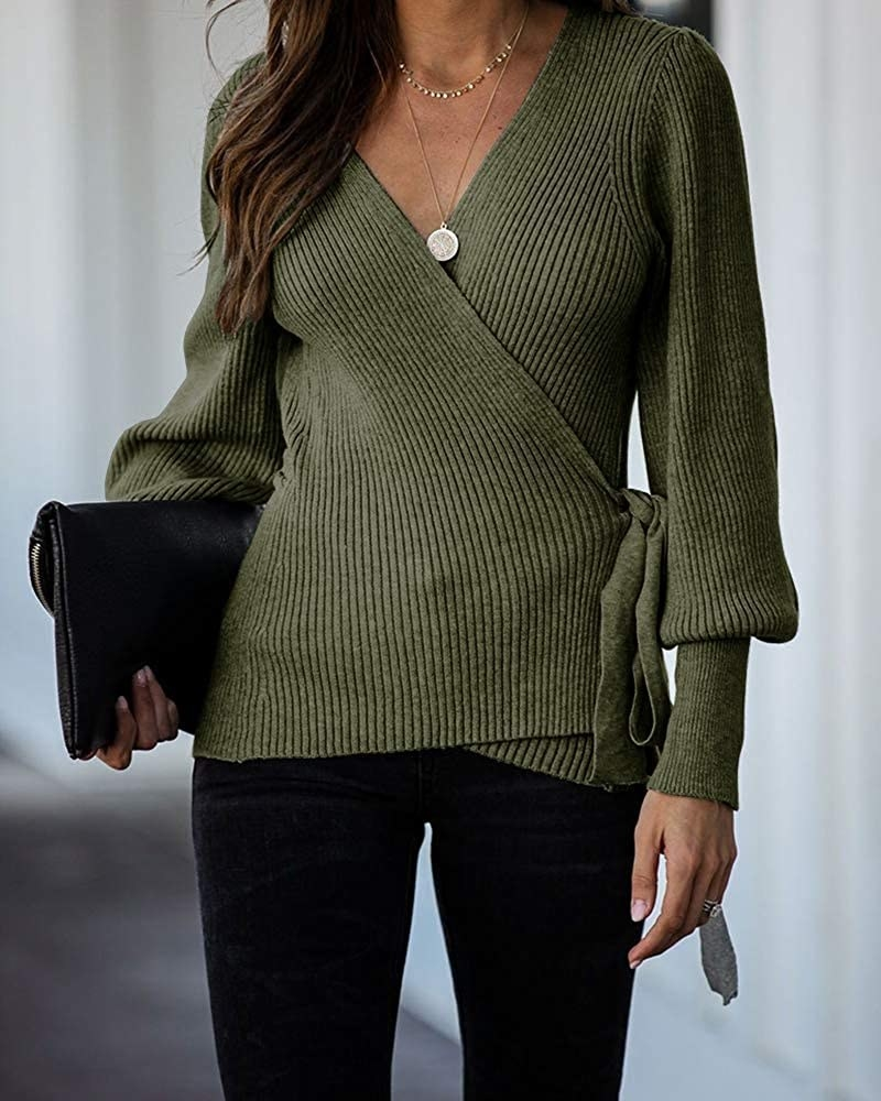 model wearing the green wrap sweater while holding a black clutch